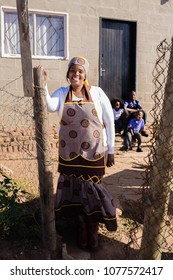 African mother in her traditional clothes infront of her township house.