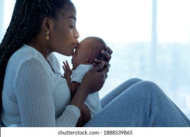 African mother holding and kissing her 21 days baby boy while sitting on bed at home, mother and little kid relaxing at home