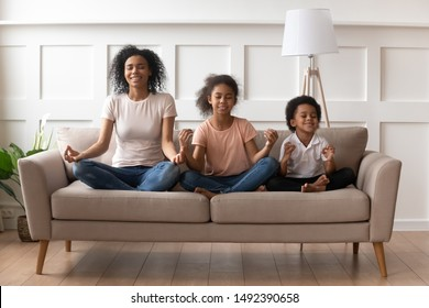 African mother little son pre-teen daughter sit on sofa in lotus pose doing yoga practise meditation, yogini woman mom teach to kids reach Zen, funny activities at home, mental physical health concept