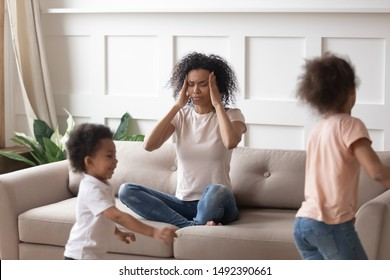 African mother sit on sofa closed eyes touch temples having severe headache or migraine because of noise of little crazy children running near her. Tired exhausted mom, upbringing difficulties concept