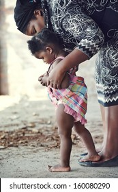 African mother teaching baby to walk in rural setting