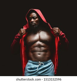 African muscular fighter in red hoodie over black studio background