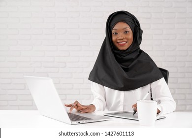 African muslim business lady working on computer in office, looking at camera, smiling. Beautiful, young african model sitting at white table, using laptop.