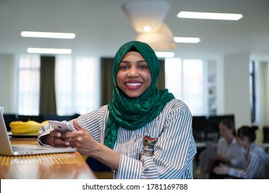 african muslim business woman wearing a green hijab using mobile phone while working on laptop computer in relaxation area at modern open plan startup office. Diversity, multiracial concept