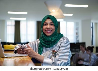 afrikanische Mulim-Geschäftsfrau, die einen grünen Hijab trägt und dabei Mobiltelefon benutzt, während sie am Laptop-Computer im Entspannungsbereich bei einem modernen Open-Plan-Startbüro arbeitet. Vielfalt, multiethnisches Konzept