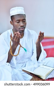 African Muslim Man Making Traditional Prayer To God While Wearing A Traditional Cap Dishdasha