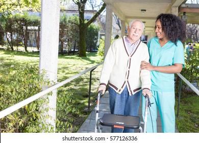 African nurse assisting elderly man with walker outdoor.