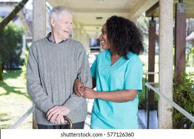African nurse assisting elderly man outdoor.