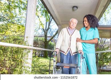 African nurse helping elderly man with walker in rehab facility hallway.