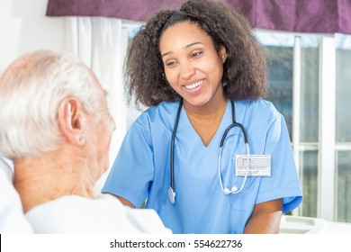 African nurse smiling to elder male patient.