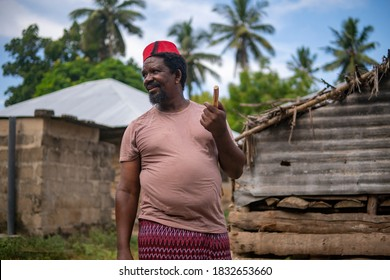 An African Older Man in Red Muslim Taqiyyah Fez Hat posing with a stick for lame people on Yard Near the Basic Hut with Thatched roof in Small Remote Village in Tanzania, Pemba island, Zanzibar