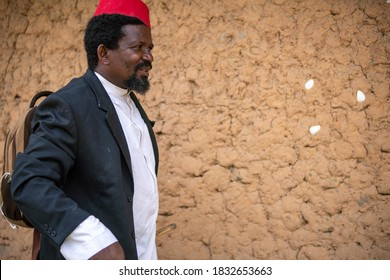 An African Older Man in Red Muslim Taqiyyah Fez Hat And Blazer on white Dress Moving a stick for lame people Near the Basic Hut with Thatched roof in Small Remote Village in Tanzania, Pemba island