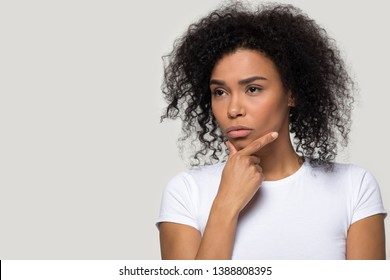 African pensive female isolated on grey blank looking aside copy space for your text, touch chin lost on thoughts thinking lady in white t-shirt planning future make business decision dreaming concept