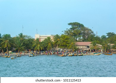 African people and boats on the shoreline of Banjul in Gambia, West Africa