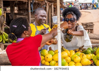 african people in a market scene, a man using his phone and credit card, a woman paying with cash for fruits