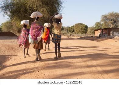 African Pokot girls leave the market in Amudat, Karamoja, carrying bags with food. Uganda, Africa.