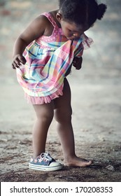 African poverty toddler with one shoe  standing in rural area cute portrait
