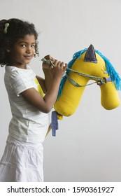 African preschool girl riding hobby horse