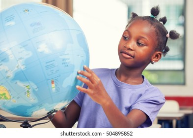 African primary school girl studying world globe in the classroom.Environment concept.