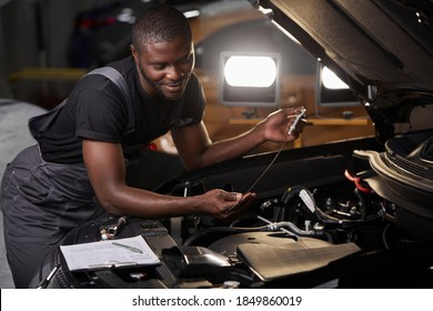 african professional auto service technician in uniform standing near car hood repairing and using check list for car inspect, indoors