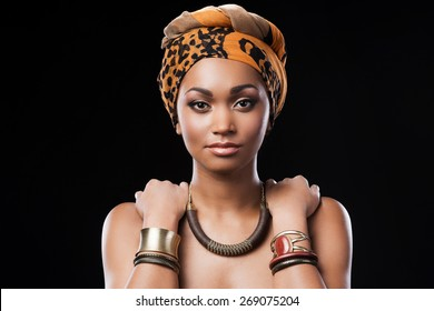 African queen. Beautiful African woman wearing a headscarf and touching her shoulders while standing against black background