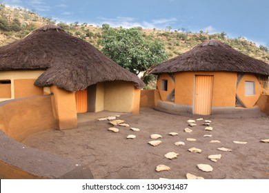 African round huts rondavels with courtyard in the Basotho tribe village. South Africa. Traditional clay houses with the straw covered roof. Drakensberg mountains surrounding. Ethnic buildings.