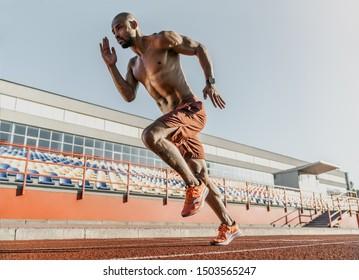 African runner athlete sprinting on running track at the stadium