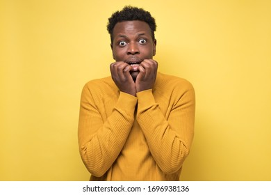 African scared guy biting nails, gawp at camera see something terrible, sensitive cowardly man watching thriller. Mental problem during quarantine. Scared to be alone.