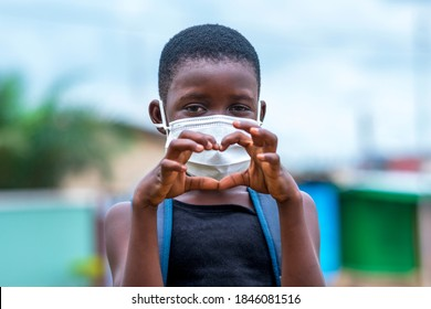 An African school child wearing face mask and showing love sign with hands-
