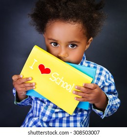 African schoolboy portrait, cute little child with holding book with text: i love school, on blackboard background, for the first time in first class