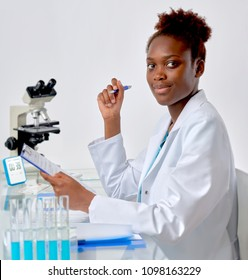 African scientist, medical or or graduate student. Bright, confident young woman in lab coat inerrupted her work to look at the viewer.