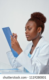 African scientist, medical or or graduate student. Confident young woman wearing lab coat holds a pen and a notepad, focus on the eyes