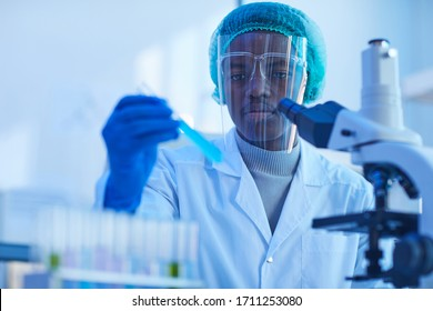 African scientist in protective gloves holding test tube with blue liquid while working with microscope