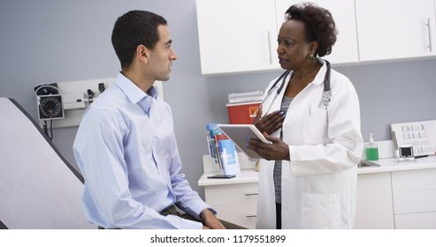 African senior medical doctor using elctronic notebook to take notes of patient