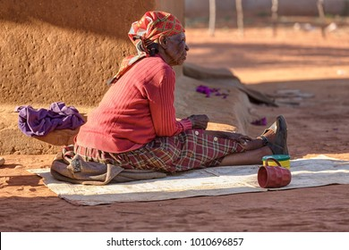 African senior woman sitting in front of the house in the village, Botswana