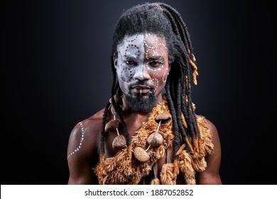 afrikanischer Shirless-Typ mit buntem Make-up einzeln auf dunklem Studiohintergrund, junger männlicher Stamm hat ethnisch traditionelle Kette