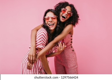 African sisters with dark curls are having fun in wonderful mood. Portrait of embracing girls with beautiful appearance