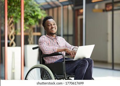 African smiling man sitting in wheelchair and using laptop computer in the mall