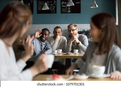 African smiling millennial man waving hand saying hello greeting young women meeting in cafe sitting at tables nearby, multiracial guys flirting with girls hanging in public place, encounter concept