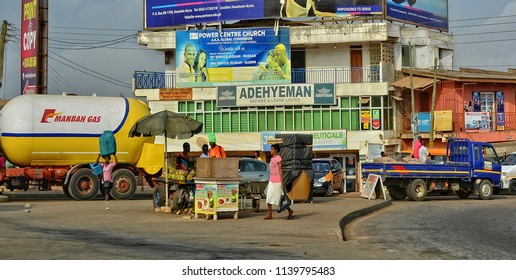 African street with people, vendors, shops, advertisement, cars and a truck along a road. City life in West Africa. Lifestyle in developing countries. Urban landscape. Ghana, Accra – January 11, 2017