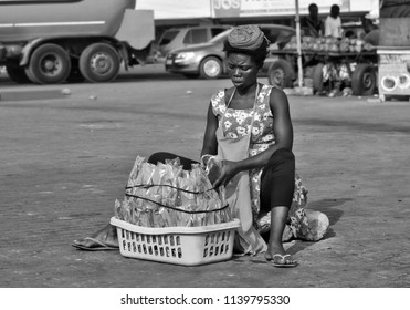 African street vendor sells local products. African woman. Ordinary life in African town. Lifestyle in developing countries. Black White Photo. Street market in Ghana. Accra, Ghana - January 11, 2017