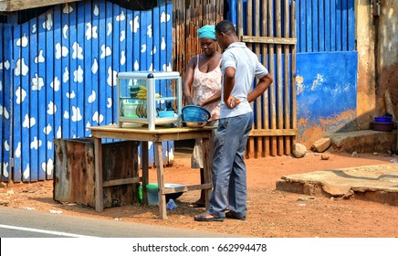 African street vendor sells local products. Street stall with food in West Africa. Ordinary street life in African town.  Accra, Ghana - January 19, 2017