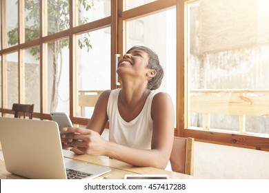 African student girl laughing out loud using smartphone, chatting with her friends online, having fun, sitting at a cafe with notebook with blank copy space for your advertising content on the table