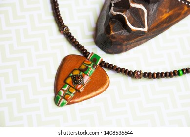 African style flat lay with necklace and wooden mask.