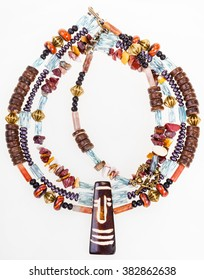 african style necklace from natural chipping gemstones (mookaite, jasper), carved bone and coconut, glass beads, brass balls on white background