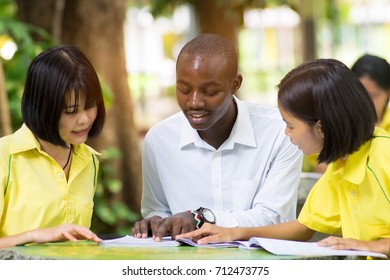 African teacher teaching asian student about foreign languages.