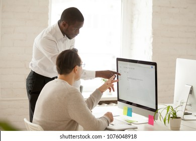 African team leader helping colleague with computer work explaining coworker new corporate application usage, black mentor teaching intern supervising and giving instructions about emails in office