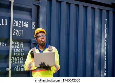 African technician dock worker in protective safety jumpsuit uniform and with hardhat and use laptop computer at cargo container shipping warehouse. transportation import,export logistic industrial