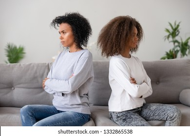 African teen daughter and mother sitting separately on couch after quarrel, upset older younger sisters with arms crossed ignore each other. Conflict and misunderstanding bad strained relation concept