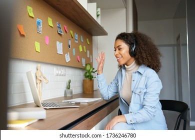 African teen girl student wear headphones waving hand video conference calling online on laptop computer at home office. Elearning zoom app video call, distance videoconference class with teacher.